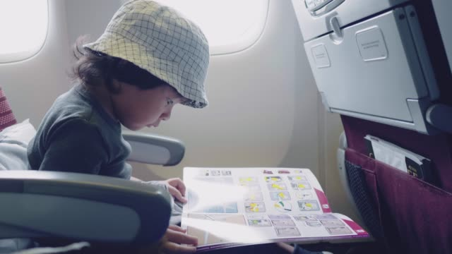 Asian baby boy reading book on airplane flight.