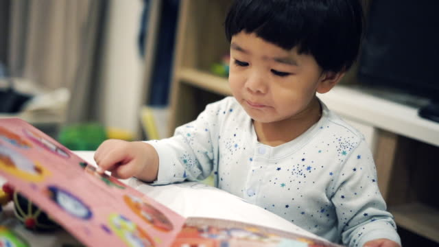 Asian baby boy reading book video