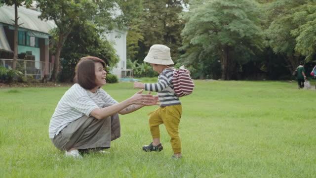 アジアの赤ちゃん男の子は、彼女を抱っこする母親の手に実行しています。 - 新学期点の映像素材/bロール