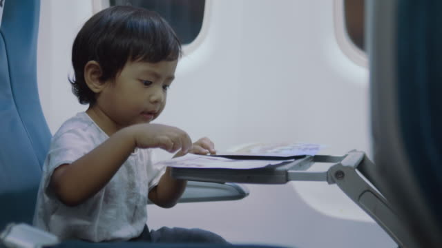 asian baby boy sitting on airplane - sedili aereo video stock e b–roll