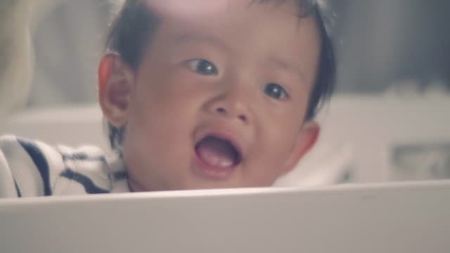 Asian baby boy standing in crib and laughing video