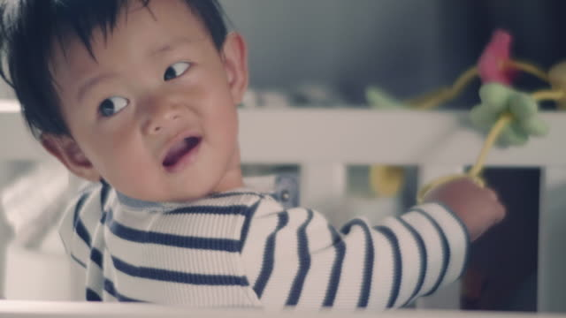 Asian baby boy standing in crib and looking at mother video