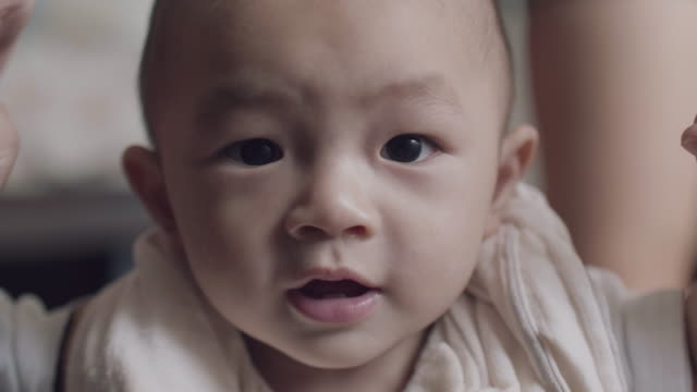 Asian baby boy taking first steps with the support of his mother video