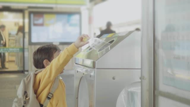 asian baby boy throwing out plastic bottle into recyclable bin - odzyskiwanie i przetwarzanie surowców wtórnych filmów i materiałów b-roll