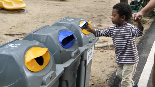 asiatische baby junge wirft plastikflasche in recycelbaren behälter - altglas stock-videos und b-roll-filmmaterial