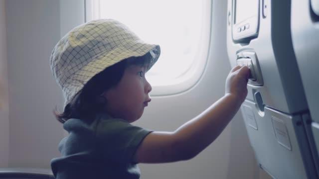 vídeos de stock e filmes b-roll de asian baby boy watching tv of airplane during flight - tv e familia e ecrã