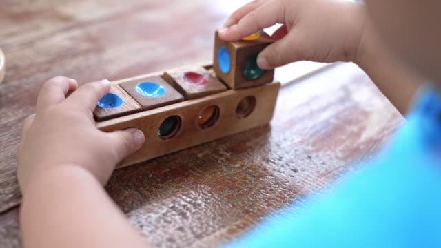asian baby boys playing wood toys - klocek filmów i materiałów b-roll
