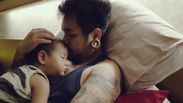 asian baby boys sleeping with father in bedroom. - tatuaggio video stock e b–roll