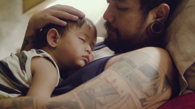 asian baby boys sleeping with father in bedroom. - neonati maschi video stock e b–roll
