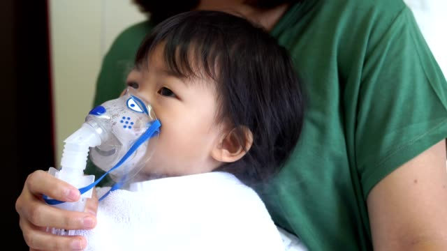 Asian baby girl breathing treatment with mother take care. video