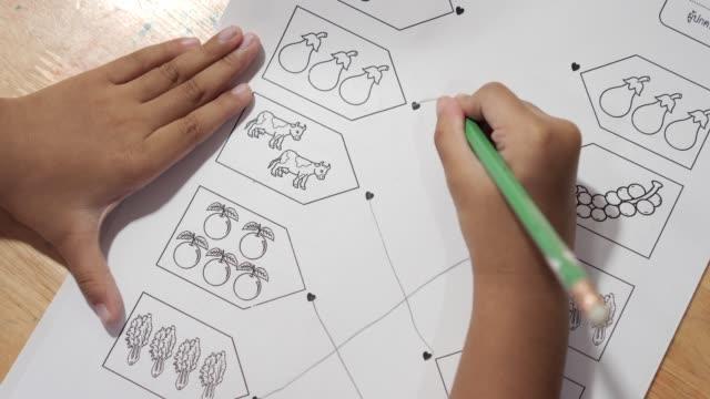 asyalı kız bebek ilkokul çağında i̇ngilizce ödev yapıyor. - çalışma kitabı stok videoları ve detay görüntü çekimi