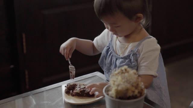 アジアの女の子は、カフェでブラウニーを食べることを楽しみます。 - 不健康な食事点の映像素材/bロール