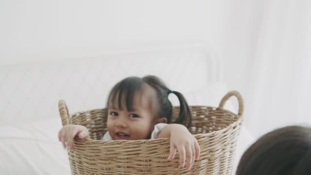 stockvideo's en b-roll-footage met aziatische meisje verstopt in de mand, terwijl haar broer wil om samen te spelen - alarm, home,