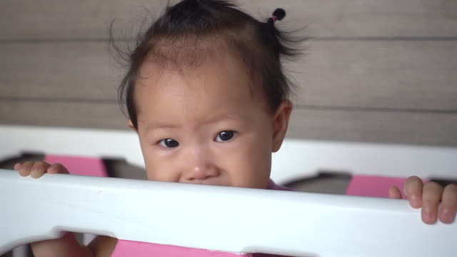Asian baby girl is crying on baby cot. video