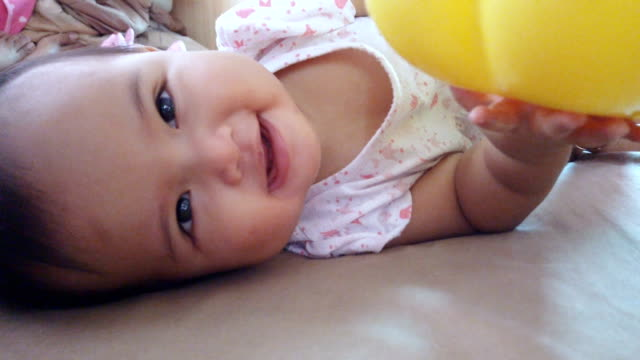 Asian baby girl lying and rolling over on bed