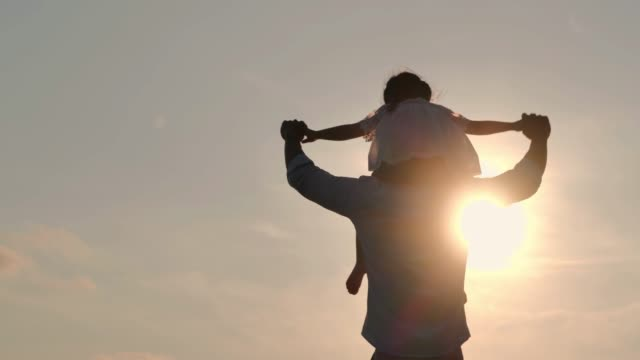 asian baby girl ride the neck of father.dad and baby girl playing together outdoors on a summer.happy family watching the sunset on the beach.holiday travel concept.vacations - istock - attività del fine settimana video stock e b–roll