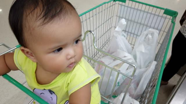vídeos y material grabado en eventos de stock de asiática bebé niña esperando padre en el carrito de compras - snack aisle
