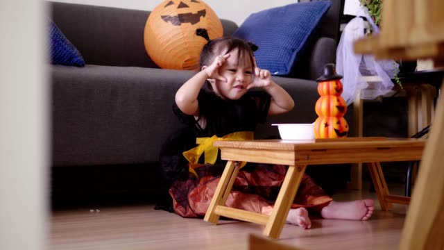 Asian baby girl with pumpkin toy while eating and singing song with mother at home