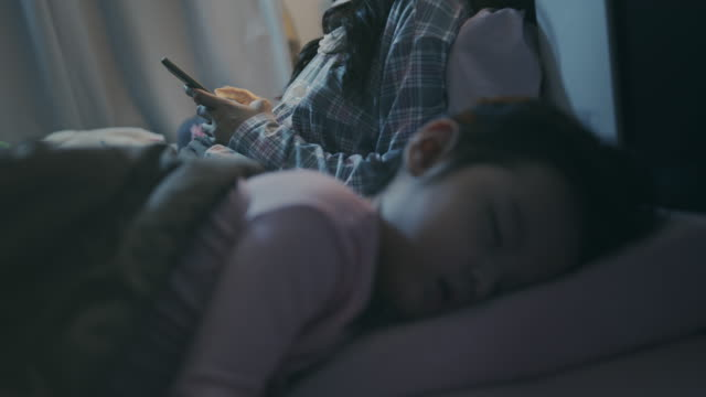 vídeos de stock e filmes b-roll de asian baby or child girl sleeping with her mother in the bedroom at night while mother playing smart phone on bed. she tired from playing all day - baby super hero