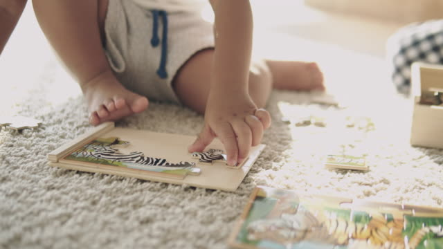 Asian baby play jigsaw on the floor.