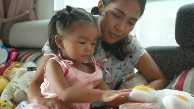 asiatisches baby spielen und buch mit mutter - alleinerzieherin stock-videos und b-roll-filmmaterial