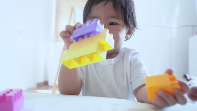 Asian baby playing colorful plastic bricks Asian baby playing colorful plastic bricks in room, baby boy enjoy playing colorful plastic bricks. playroom stock videos & royalty-free footage