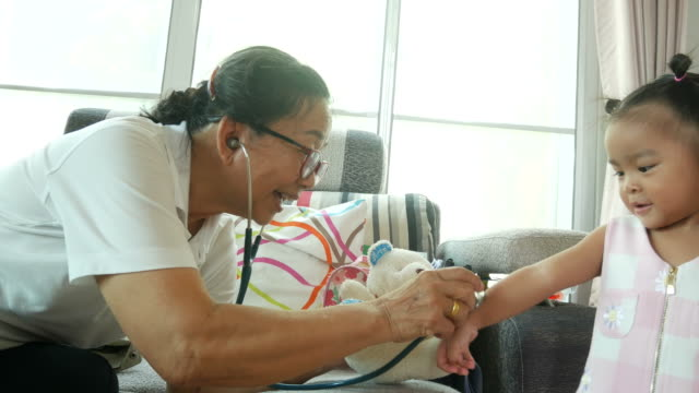 Asian baby playing doctor and patient  with grandmother video