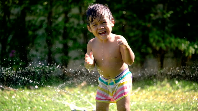 slo mo asian baby plays water smiling and looking to camera. - 2 3 anni video stock e b–roll