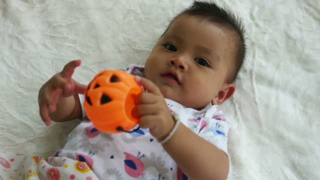 Asian baby smiling with pumpkin toy