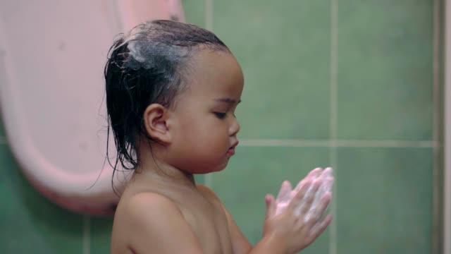 Asian baby taking a shower washing her hands