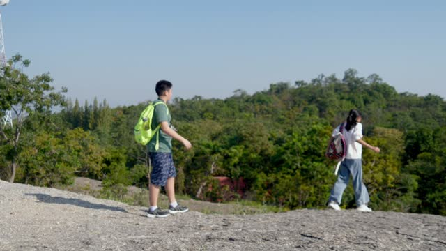 Asian backpacker children hiking the top of mountain together in sunny day, outdoor adventure concept.