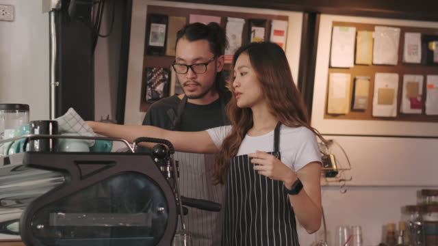 vídeos de stock e filmes b-roll de asian barista waiter check inventory and talking with colleague at counter bar,food and drink business concept,small business concept.restaurant worker - training