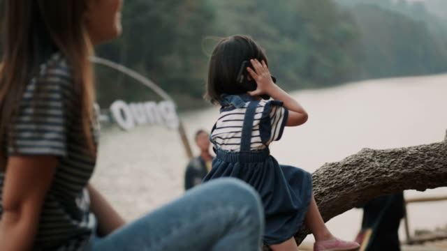 Asian beautiful baby girl with her mother is using smartphone while playing and talking with her positive expression on vacation time beside the river and greenery space video