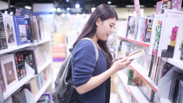 Asian beautiful college student working in library
