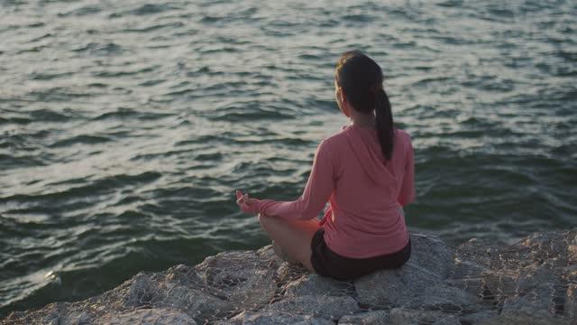 Asian beautiful girl sports girl training meditation sitting on stones seaside during sunset.