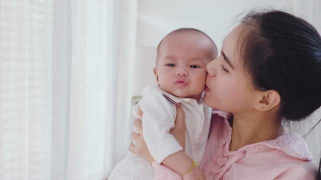 Asian beautiful mother giving warm hugs little baby girl in arms holding softly then kiss young kid in bedroom at home. Soft touch, love care, protection of mom and child in family relationship.