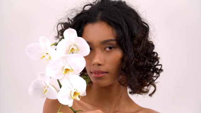 Asian beautiful tan woman is beautiful as  Phalaenopsis orchid on white background. People with beauty, healthcare, emotion concept.
