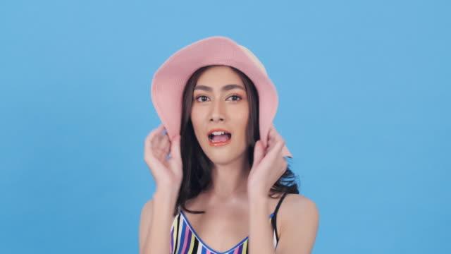 ピンクの帽子をかぶったアジアの美しい女性幸せな感情の笑顔。新鮮な感じ美しい女性。美容、ファッション、旅行、ショッピングのコンセプト。 - スーパーモデル点の映像素材/bロール