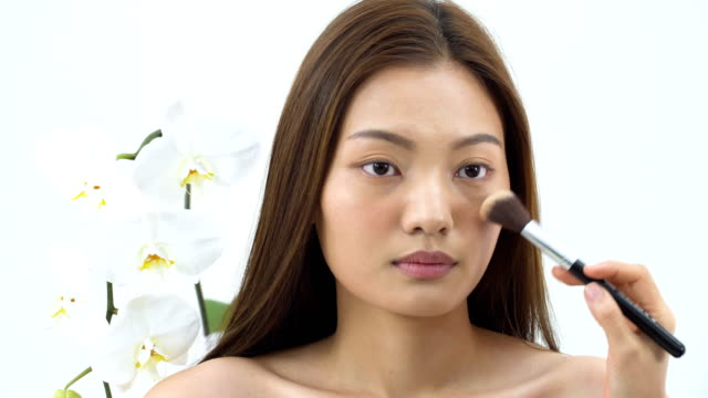 Asian beautiful woman is made up with Blush brush  on cheek to be beautiful as Phalaenopsis orchid on white background. People with beauty, healthcare, emotion concept.