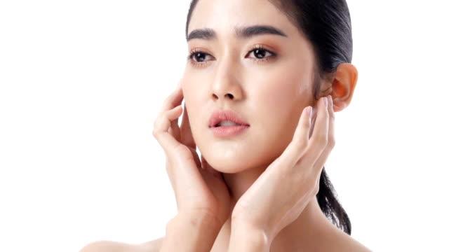 アジア美人が白い背景で彼女の顔に触れます。美容、メイク、健康管理の概念を持つ人々。 - 人の肌点の映像素材/bロール