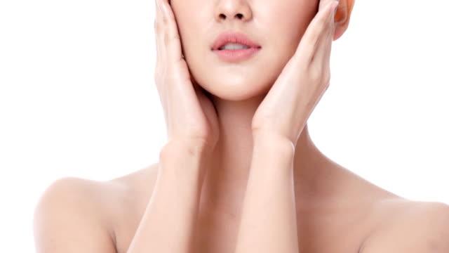 vídeos de stock, filmes e b-roll de mulher linda asiática tocando seu rosto em fundo branco. pessoas com beleza, maquiagem, conceito de cuidados de saúde. - skincare