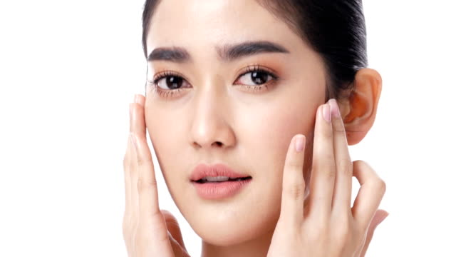 vidéos et rushes de asiatique belle femme toucher son visage à fond blanc. personnes atteintes de beauté, maquillage, soins de santé concept. - perfection