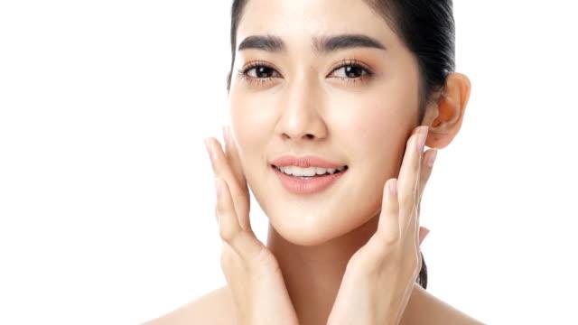 schöne asiatin mit attraktiven lächeln ihr gesicht zu berühren. - kosmetische behandlung stock-videos und b-roll-filmmaterial