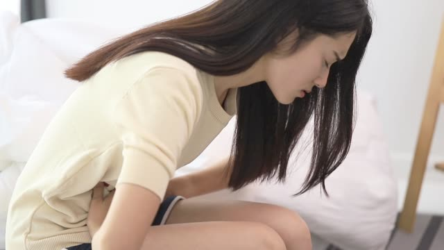 Asian beautiful women feel menstrual cramps and stomachache after menstruation.Hand holding stomach and belly after taking a medication.Problem and disorder of female body.