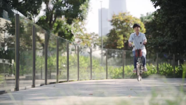 Asian beauty riding bike in city park in morning slow motion of Asian woman riding bike in city park in morning singapore architecture stock videos & royalty-free footage