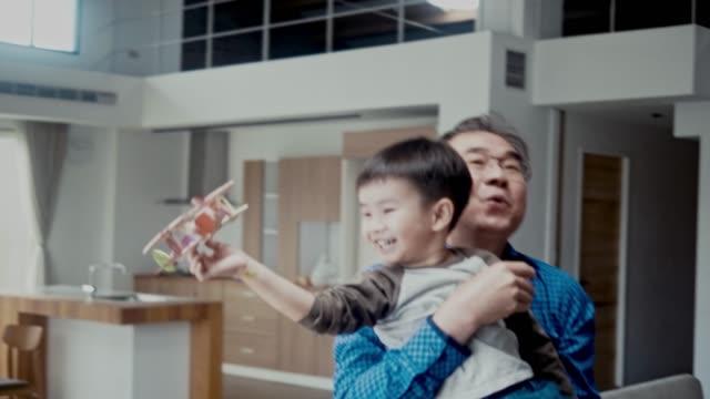 asian boy and his grandfather flying a model airplane (slow motion) - podnosić filmów i materiałów b-roll