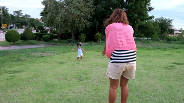 Asian boy and mother are playing at park. video