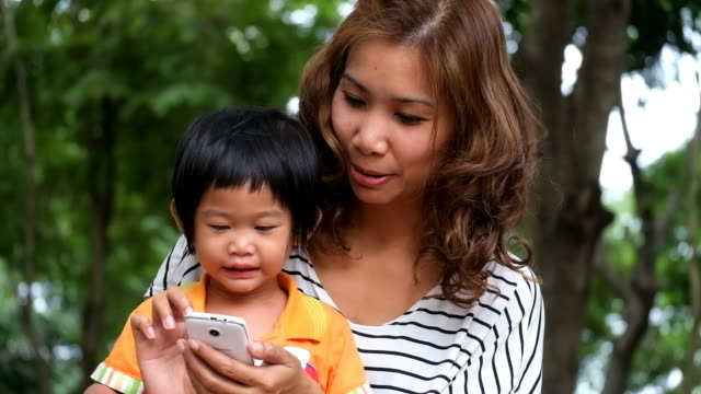 asian boy and mother are playing game on smartphone at park. - young singles stock videos & royalty-free footage
