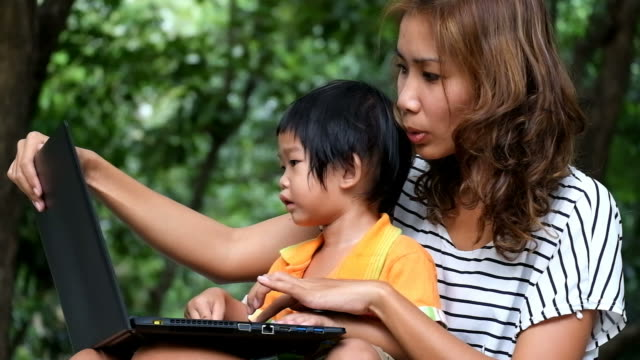Asian boy and mother are using notebook at the park. Asian boy and mother are using notebook at the park. young singles stock videos & royalty-free footage