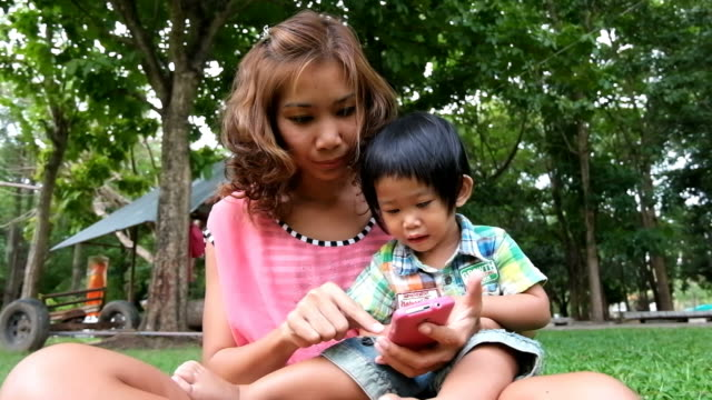 Asian boy and mother play game on smartphone at park video